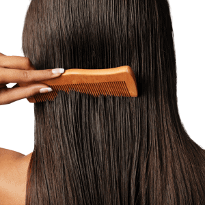 woman combing hair with wooden brush