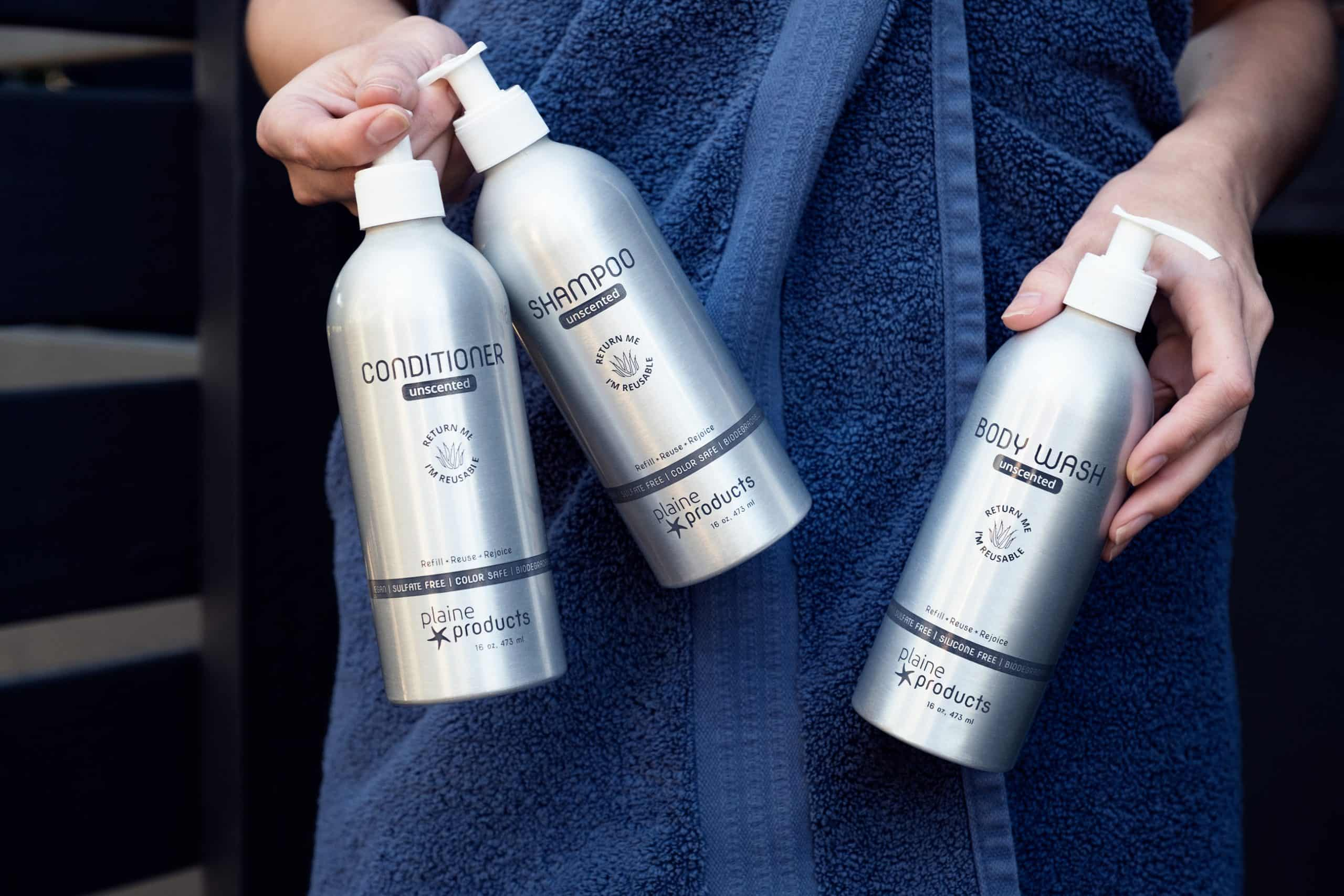Unscented Shampoo, Conditioner, and Body Wash held by a woman wrapped in a blue towel